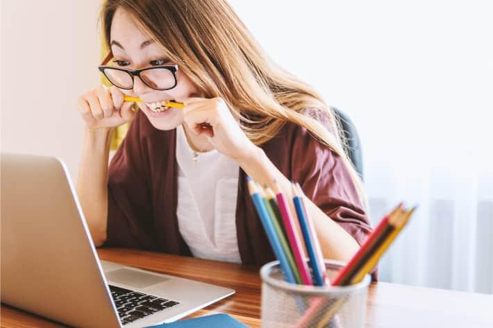 Kvinne som sitter bøyd over en bærbar datamaskin og biter i blyanten i frustrasjon