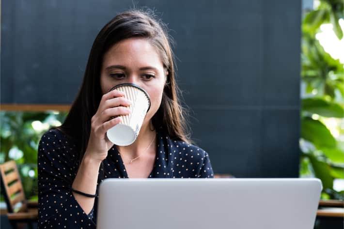 Kvinne som surfer på nettet på en bærbar datamaskin og drikker kaffe